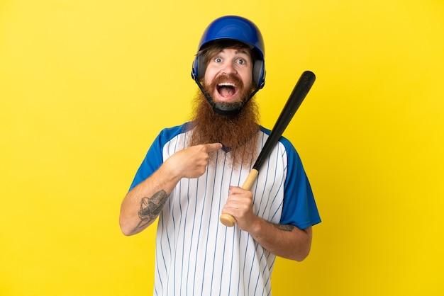 Roodharige honkbalspeler man met helm en vleermuis geïsoleerd op gele achtergrond met verrassende gezichtsuitdrukking
