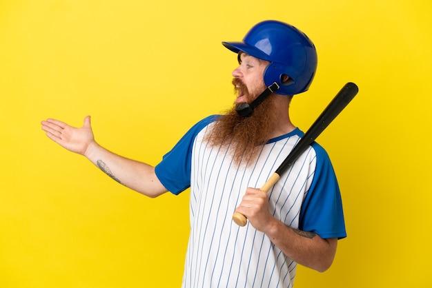 Roodharige honkbalspeler man met helm en vleermuis geïsoleerd op gele achtergrond met verrassingsuitdrukking terwijl hij opzij kijkt