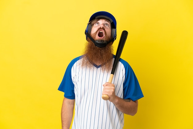Roodharige honkbalspeler man met helm en vleermuis geïsoleerd op gele achtergrond opzoeken en met verbaasde uitdrukking