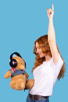 Roodharige jong schattig meisje dans kijken naar haar teddybeer met hoofdtelefoon luisteren muziek blauwe achtergrond gadget apparaat technologie concept met lege ruimte voor advertentie