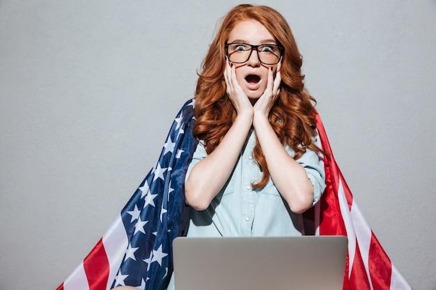 Roodharige jonge dame met de vlag van de vs met behulp van laptopcomputer