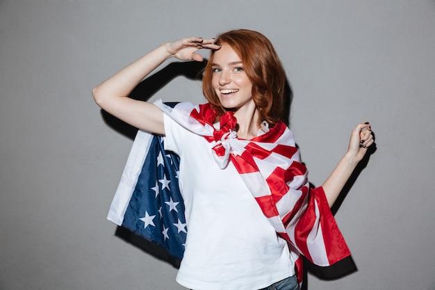 Roodharige jonge dame superheld met amerikaanse vlag.