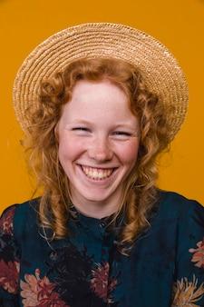Roodharige jonge vrouw die en camera lacht bekijkt