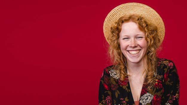 Roodharige jonge vrouw die lacht op camera op rode achtergrond