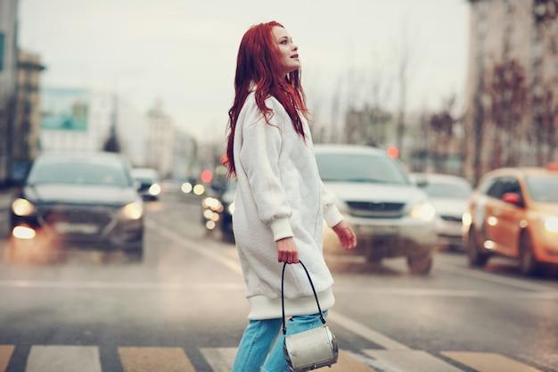 Roodharige jonge vrouw in een witte jas en spijkerbroek steekt de weg bij een zebrapad.