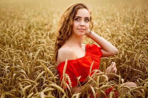 Roodharige jonge vrouw in rode jurk op tarweveld gelukkig meisje met krullend haar in veld zoete glimlach van l...