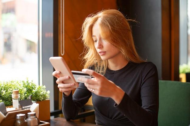 Roodharige jonge vrouw kaartbetaling via mobiele telefoon om rekeningen te betalen in een café.