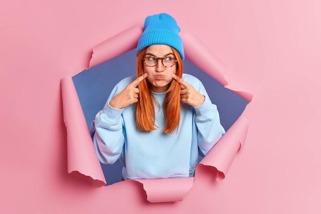 Roodharige jonge vrouw maakt grimas pruilen wangen houdt adem wijst wijsvingers op gezicht dwazen rond draagt bril blauwe hoed en trui.