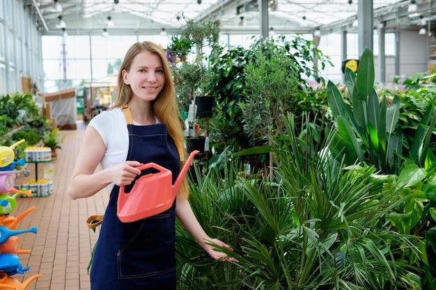Roodharige jonge werknemer in plantenmarkt