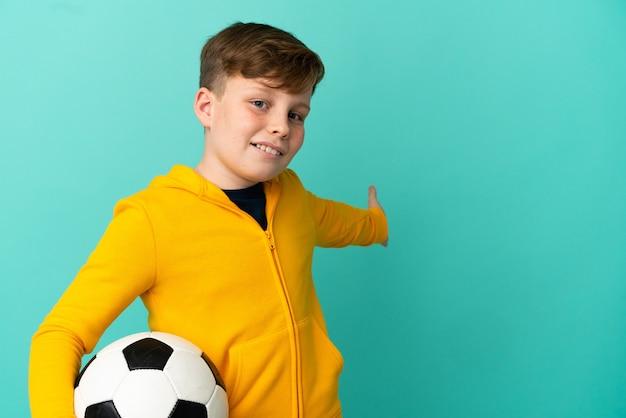 Roodharige jongen die voetbal speelt geïsoleerd op een blauwe achtergrond die zijn handen naar de zijkant uitstrekt om uit te nodigen om te komen