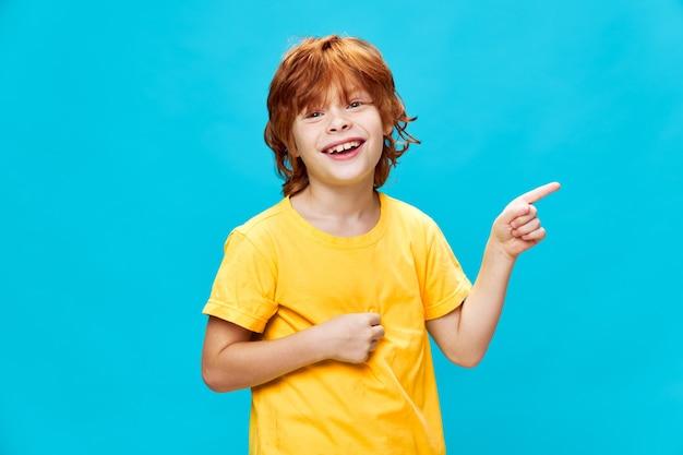 Roodharige jongen gelukkige glimlach gele t-shirt gebaren met handen jeugdmodel