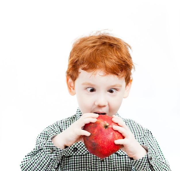 Roodharige jongen met sproeten, kijkt met grote ogen met verbazing naar een enorme rode pittige granaatappel, portret van een kind