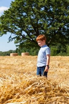 Roodharige jongen naast een stapel gouden stro in een veld