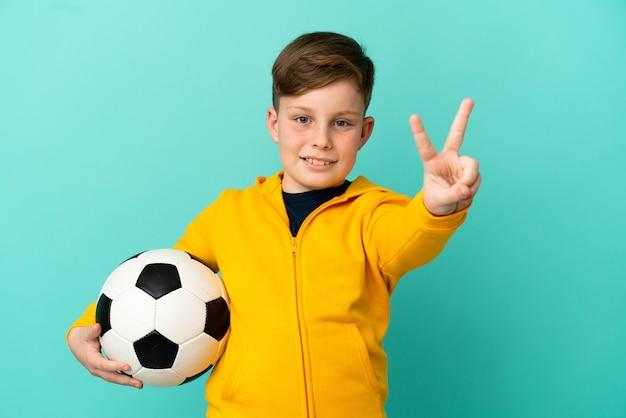 Roodharige jongen voetballen geïsoleerd op blauwe achtergrond glimlachend en overwinningsteken tonen showing