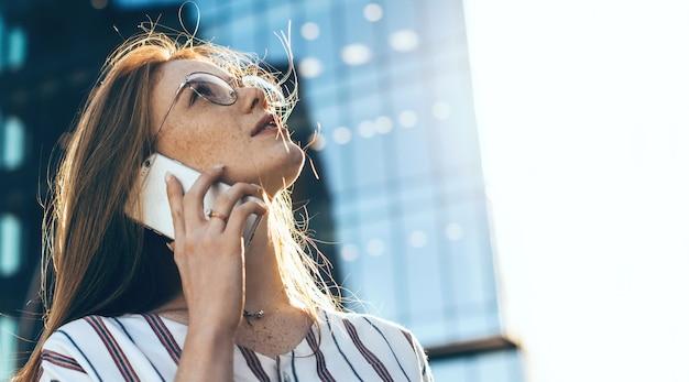 Roodharige kaukasische zakelijke dame met sproeten en bril opzoeken en praten over de telefoon in een winderige zonnige dag