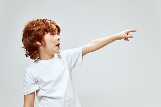 Roodharige kind verrast blik toont een vinger opzij