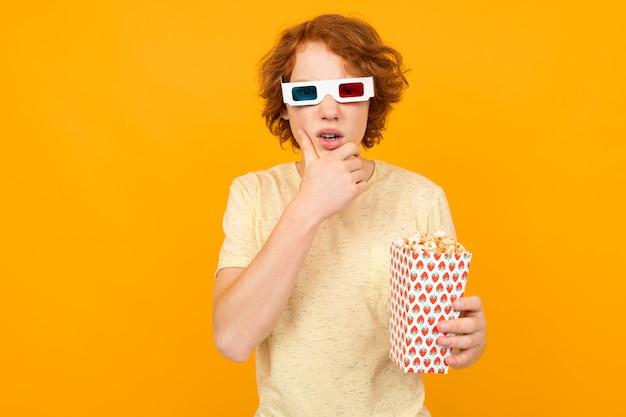 Roodharige knappe tienerjongen in t-shirt met filmglazen met popcorn in zijn handen op geel met exemplaarruimte