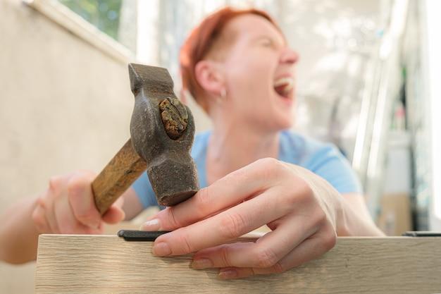 Roodharige kortharige vrouw schreeuwt van pijn en slaat zichzelf met een hamer op de vinger finger