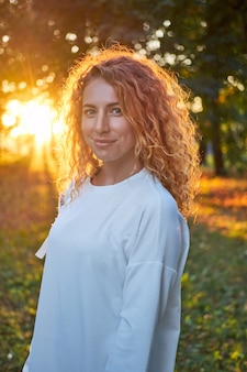 Roodharige krullend wit vrouw het glimlachen portret in zonsonderganglicht