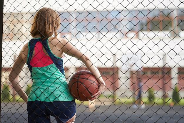 Roodharige mager kaukasisch meisje dat zich dichtbij omheining van het openluchthof van het straatbasketbal bevindt dat een bal houdt en een spel waarneemt