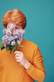 Roodharige man in oranje trui bloemen ruiken met gesloten ogen genieten van het leven zonder allergie, blauw