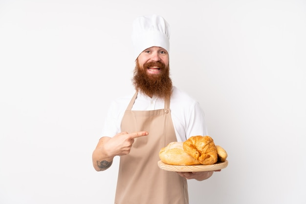 Roodharige man in uniform chef. mannelijke bakker die een lijst met verscheidene broden houdt en het richt