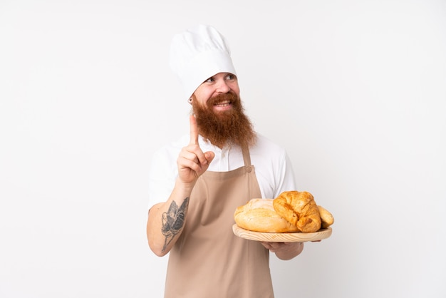 Roodharige man in uniform van de chef-kok. mannelijke bakker die een lijst houdt met verscheidene broden die de oplossing willen realiseren terwijl hij een vinger opheft