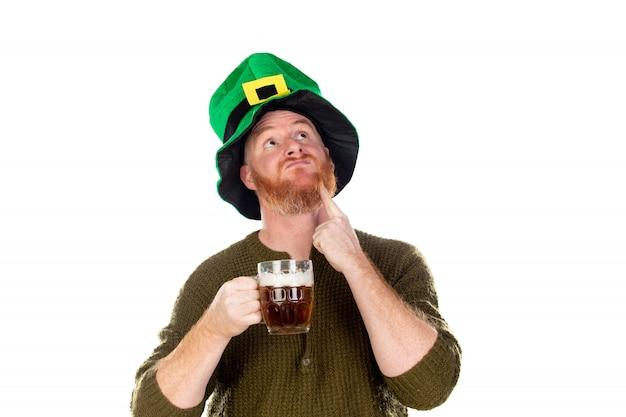 Roodharige man met een grote groene hoed een biertje drinken