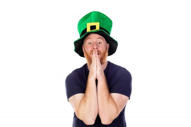 Roodharige man met groene hoed bidden