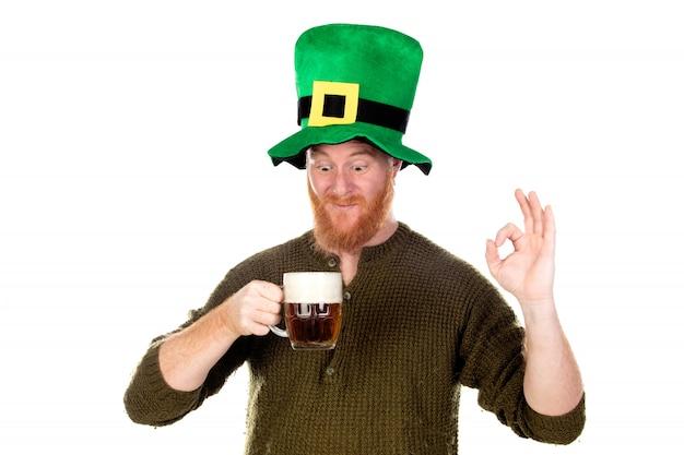 Roodharige man met groene hoed een biertje drinken
