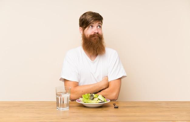 Roodharige man met lange baard en salade maken twijfels gebaar terwijl het opheffen van de schouders