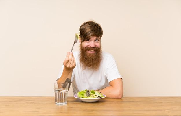 Roodharige man met lange baard en salade