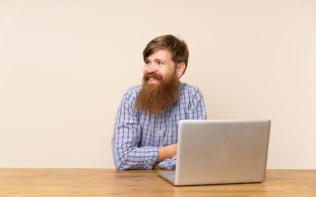 Roodharige man met lange baard in een tafel met een laptop lachen