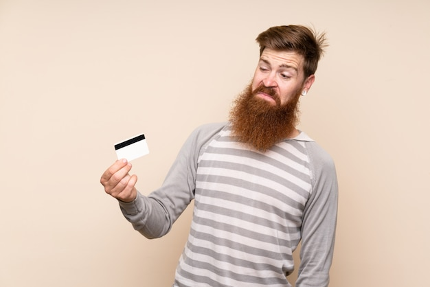 Roodharige man met lange baard met een creditcard