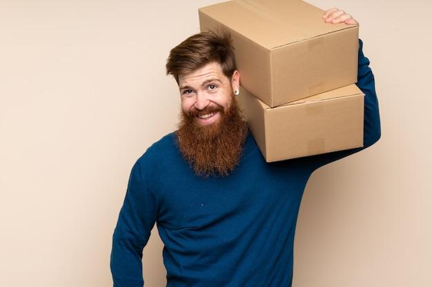 Roodharige man met lange baard met een doos om het naar een andere site te verplaatsen