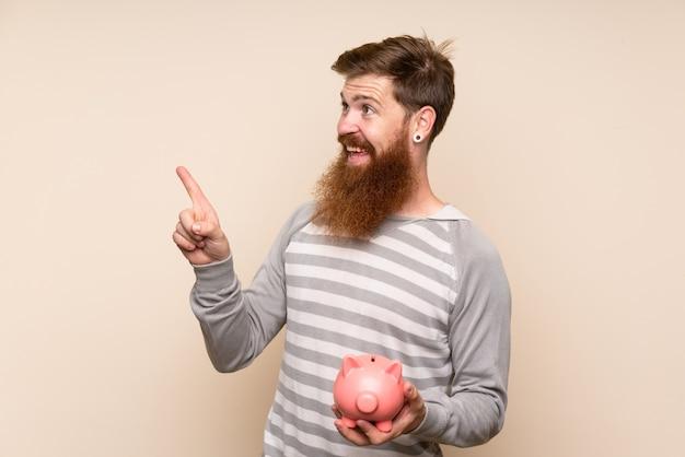 Roodharige man met lange baard met een grote spaarpot