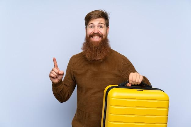 Roodharige man met lange baard met een koffer die op een geweldig idee wijst