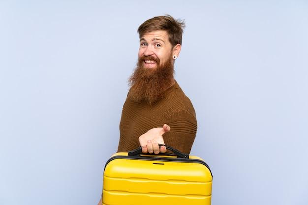 Roodharige man met lange baard met een koffer glimlachend veel
