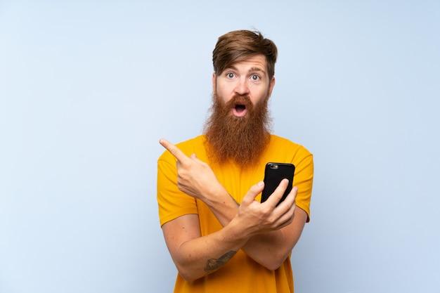 Roodharige man met lange baard met een mobiel over geïsoleerde blauwe muur verrast en wijzend kant