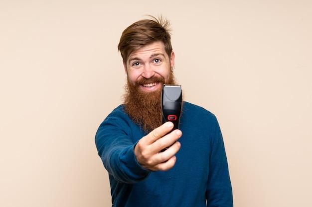 Roodharige man met lange baard met kapper of kapper jurk en haar snijmachine te houden