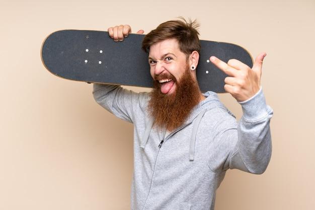 Roodharige man met lange baard met skate