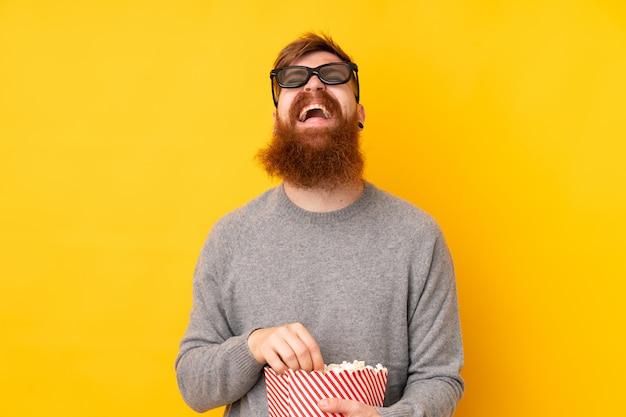 Roodharige man met lange baard over geïsoleerde geel met 3d-bril en met een grote emmer popcorns