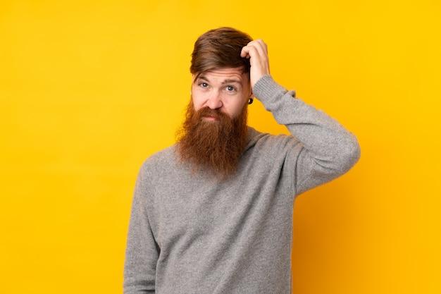 Roodharige man met lange baard over geïsoleerde gele muur met een uitdrukking van frustratie en niet begripvol