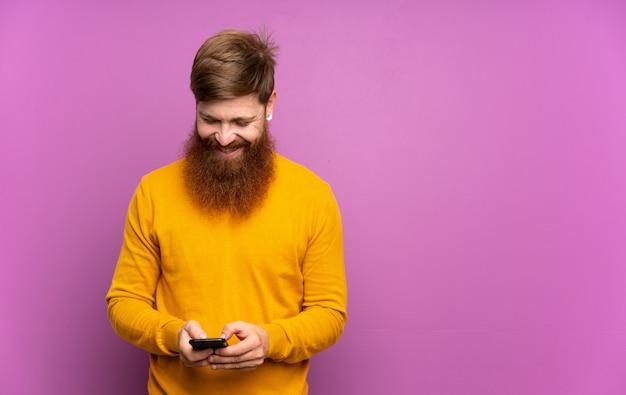 Roodharige man met lange baard over geïsoleerde paars een bericht verzenden met de mobiel