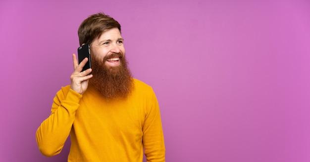 Roodharige man met lange baard over geïsoleerde paars houden een gesprek met de mobiele telefoon