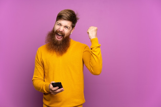 Roodharige man met lange baard over geïsoleerde paars met telefoon in overwinningspositie