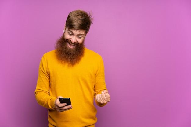 Roodharige man met lange baard over geïsoleerde paars verrast en het verzenden van een bericht