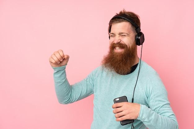 Roodharige man met lange baard over geïsoleerde roze muur luisteren muziek en dansen