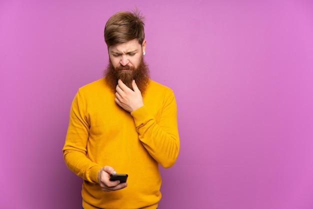 Roodharige man met lange baard over paarse muur denken en het verzenden van een bericht