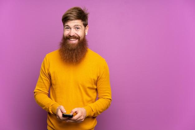 Roodharige man met lange baard over paarse muur een bericht verzenden met de mobiel